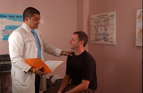Chiropractor examining patient for neck paiin