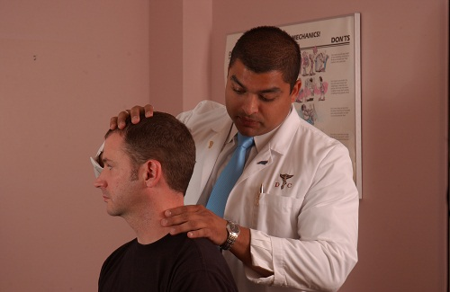 Dr.Ali  examines the neck of the patient injured from work