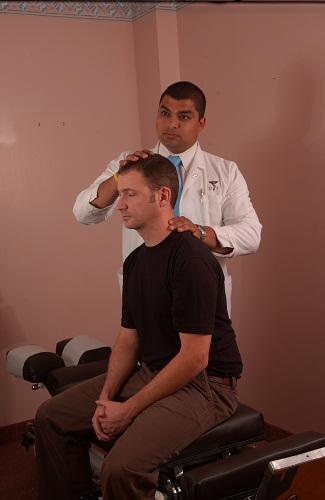 Charlotte chiropractor examining patient with neck pain