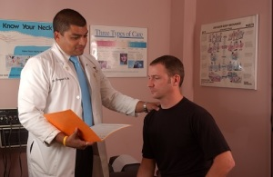 Neck pain patient examining by chiropractor