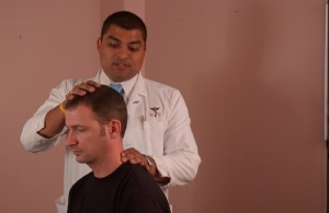 Chiropractor examining patient suffered from headache